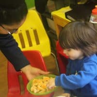 Tesco worker and child selecting a satsuma slice